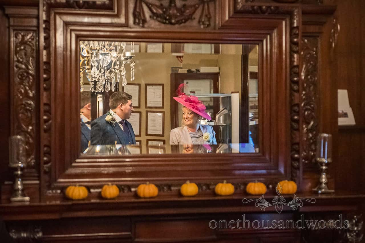 Groom and mother of the bride in pink hat framed in dark wooden mirror with autumnal pumpkin decorations photograph