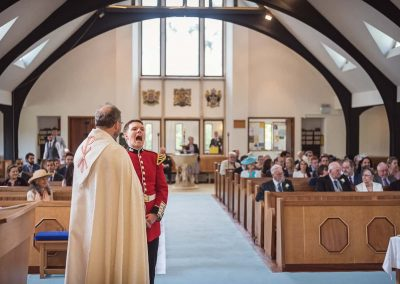 Comedy wedding photograph of military groom singing whilst waiting with vicar before church wedding ceremony
