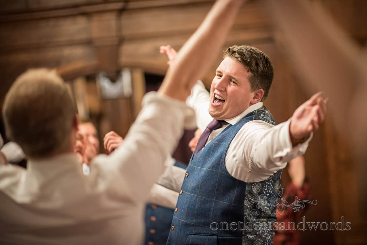 Groom wearing blue check tweed waistcoat sings along to singing waiters performance with arms in the air