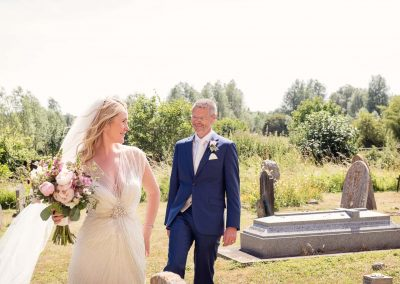 Groom smiles at bride whilst fun posing with wedding bouquet in churchyard photograph by two wedding photographers