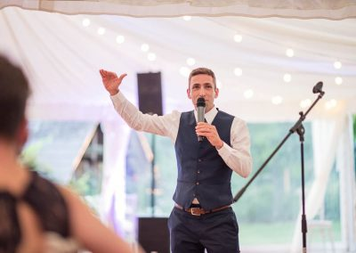 Groom makes wedding speech with microphone about his height in marquee by Dorset and Hampshire wedding photographers