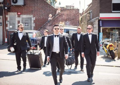 Groomsmen documentary wedding photograph of black suits on wedding morning walking like reservoir dogs film