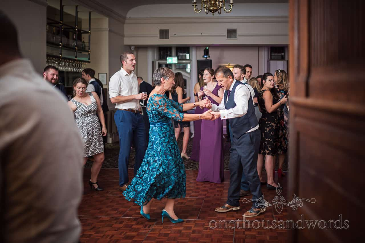 Groom's parents dancing among guests to wedding disco in New Forest hotel bar