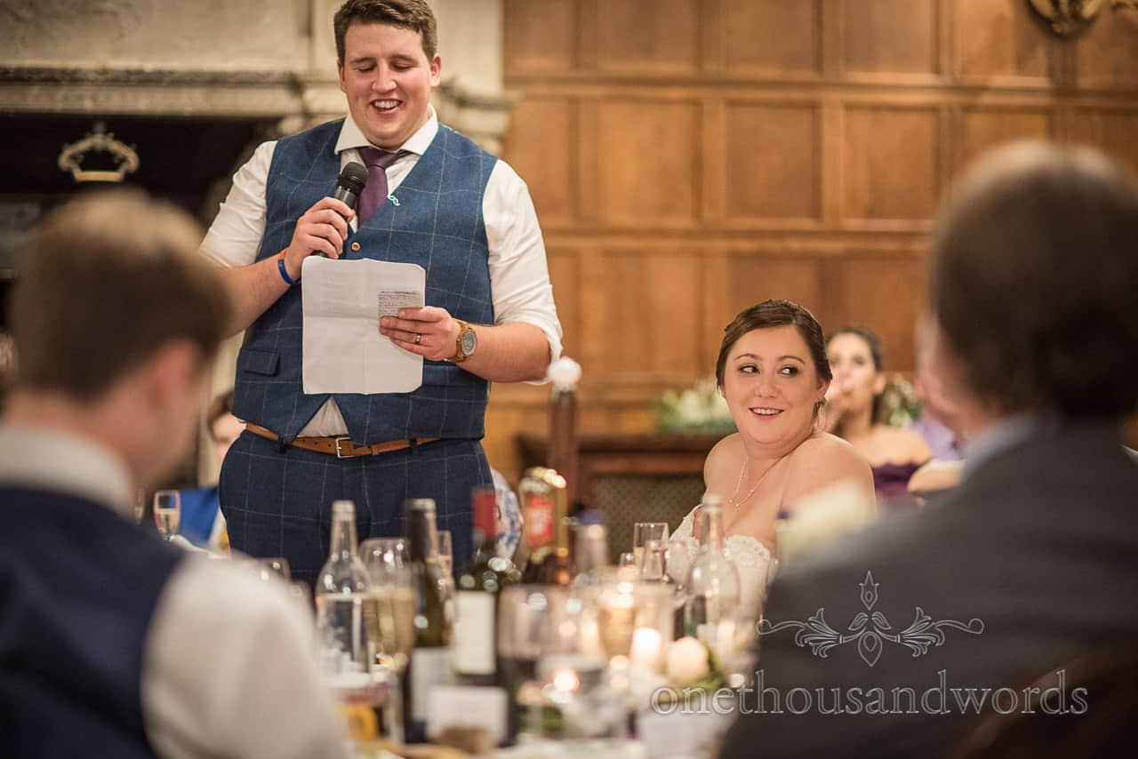 Happy groom reads wedding speech from paper notes as bride watches guests reactions from top table
