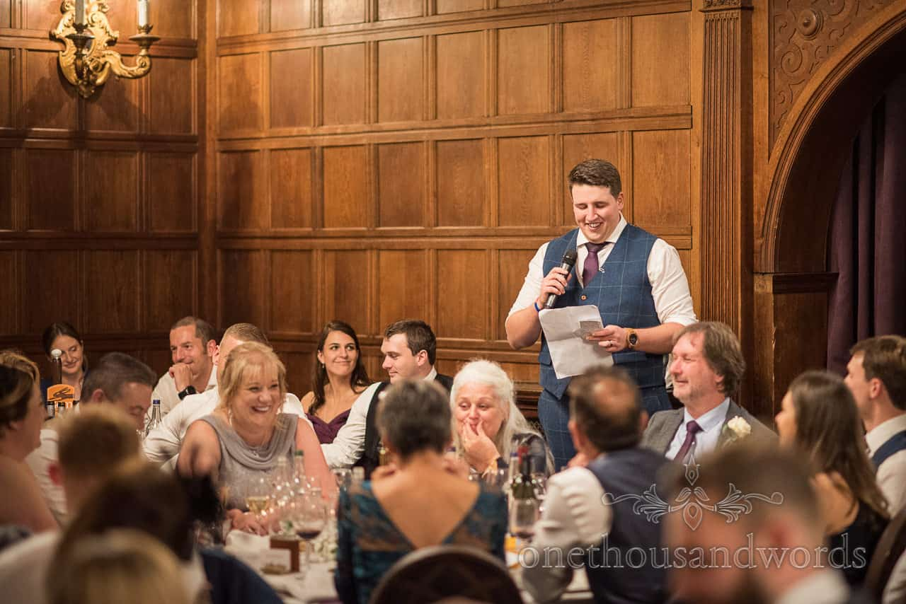 Grooms makes funny wedding speech in wooden panelled room at New Forest hotel wedding venue Rhinefield House