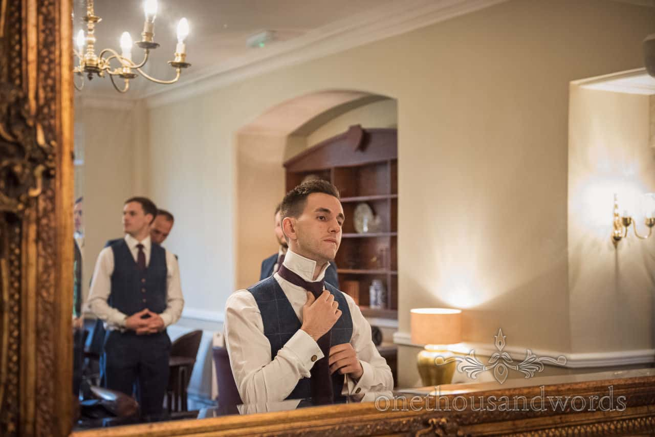 Groomsman does up burgundy tie in gold gilded mirror on wedding morning groom preparation photographs