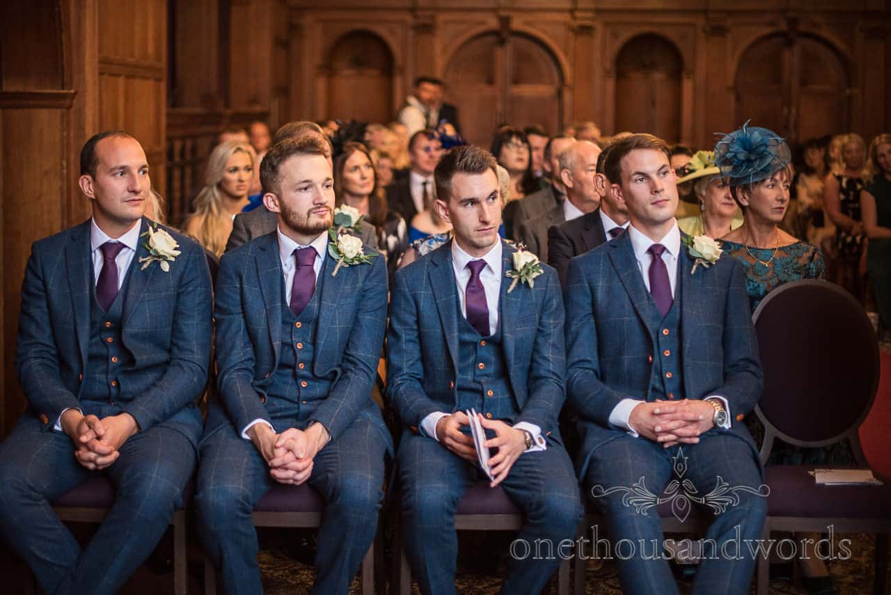 Groomsmen in blue three piece suits and purple ties sit on chairs waiting for wedding ceremony at Rhinefield House