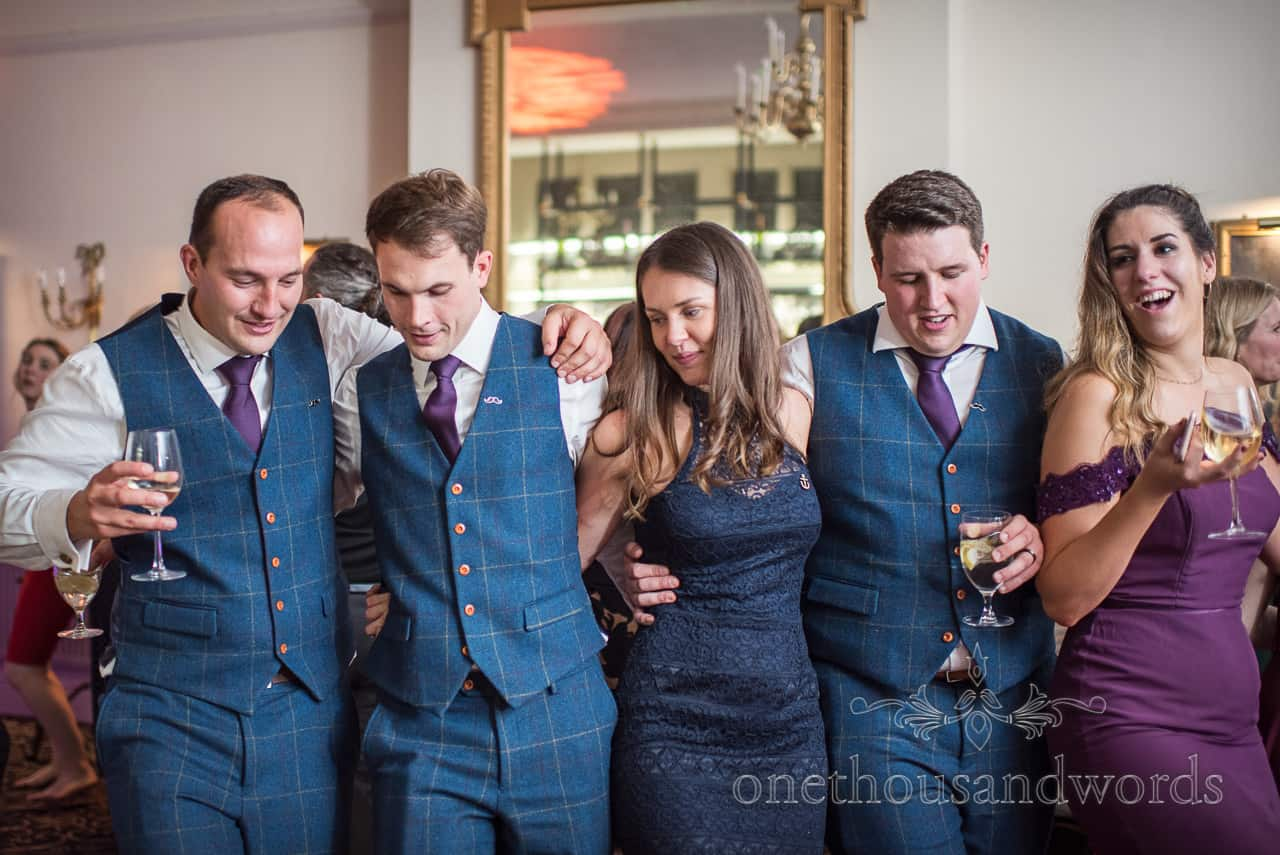 Groomsmen in blue tweed suits with bridesmaid and guest dancing in a line at New Forest wedding
