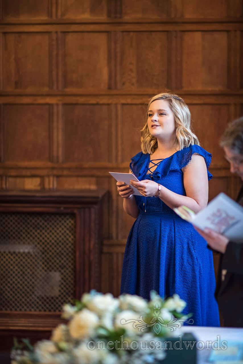 Documentary photography of female guest in blue dress delivering wedding reading against oak panelling by one thousand words