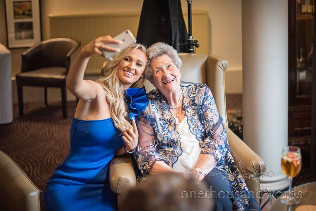 Female wedding guest in blue dress takes selfie photograph with granny at Rhinefield house wedding drinks reception