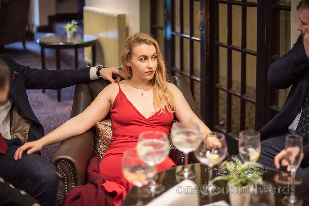Blonde female wedding guest wearing red dress photograph during drinks reception