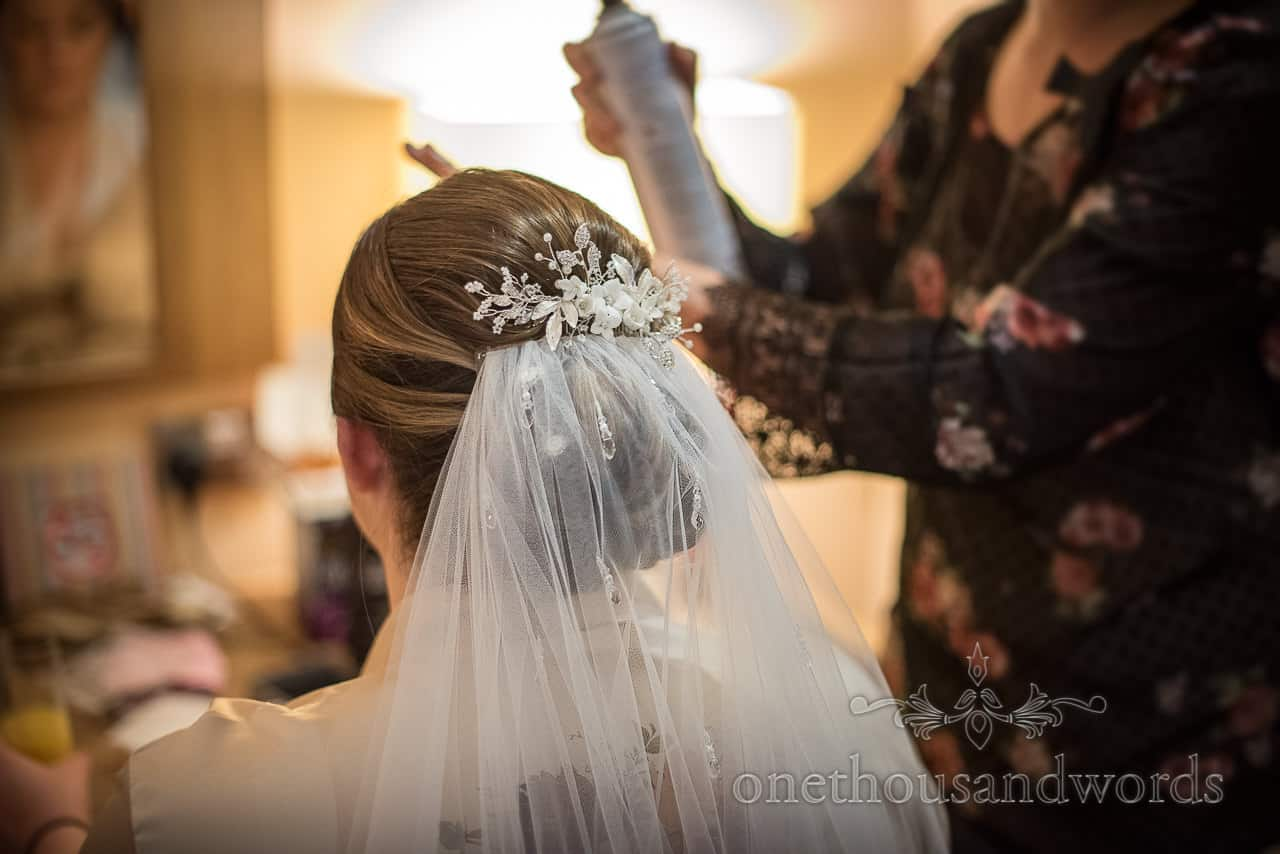 Wedding hair styling with hair spray and floral hair piece and white veil during bridal preparations by one thousand words