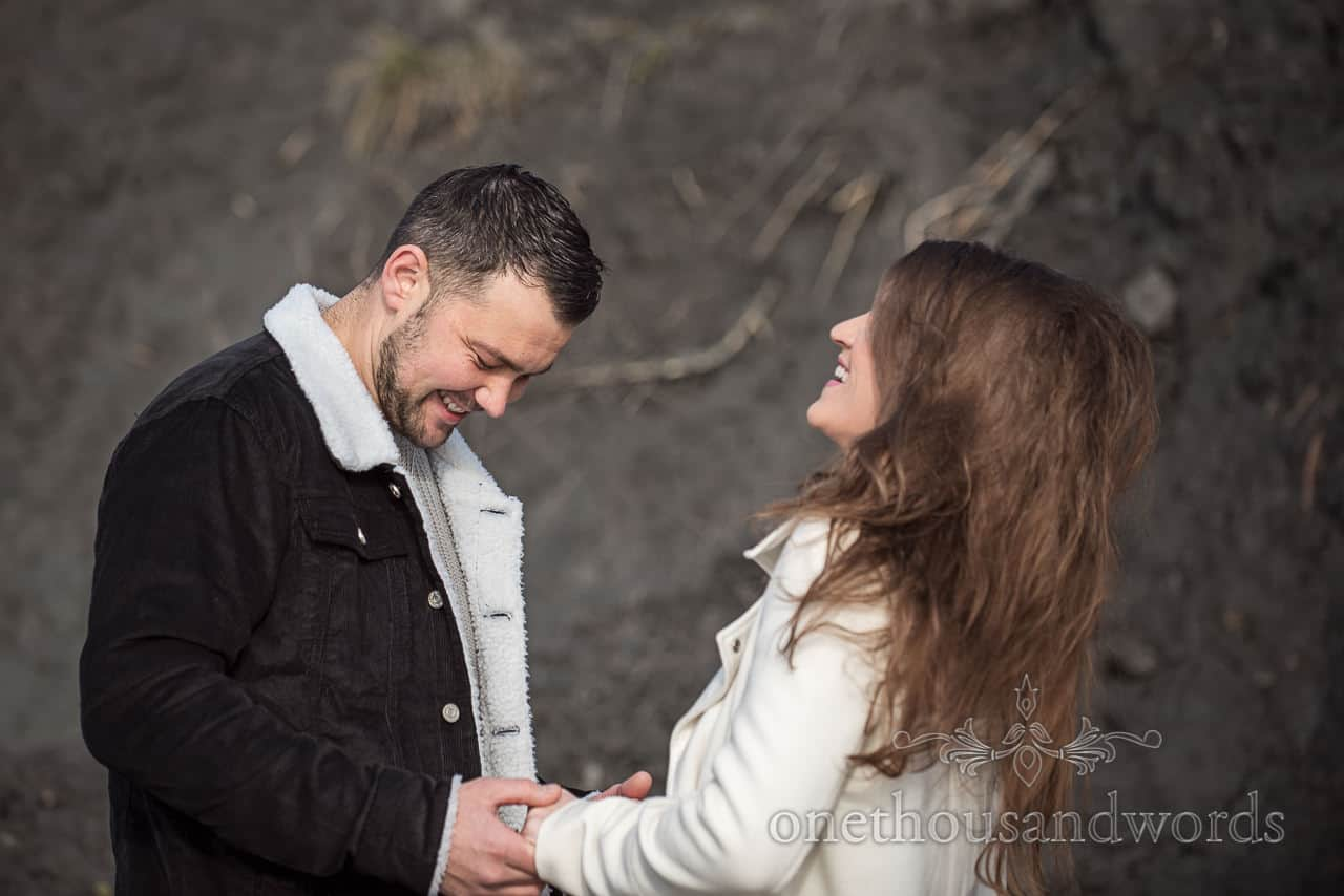Happy couple hold hands whilst laughing at engagement photo shoot with black cliff background with one thousand words photography