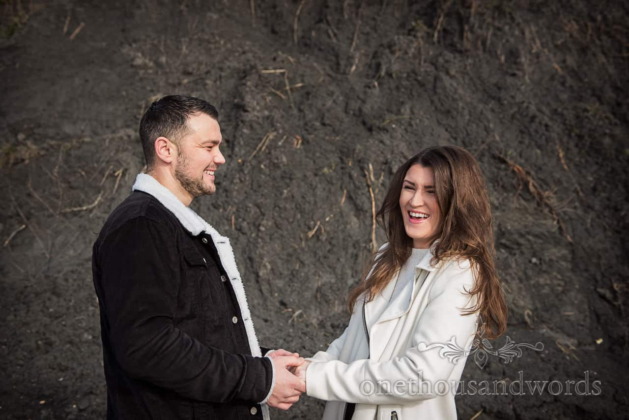Happy couple laughing at engagement shoot photograph against black cliff by one thousand words wedding photography in Dorset