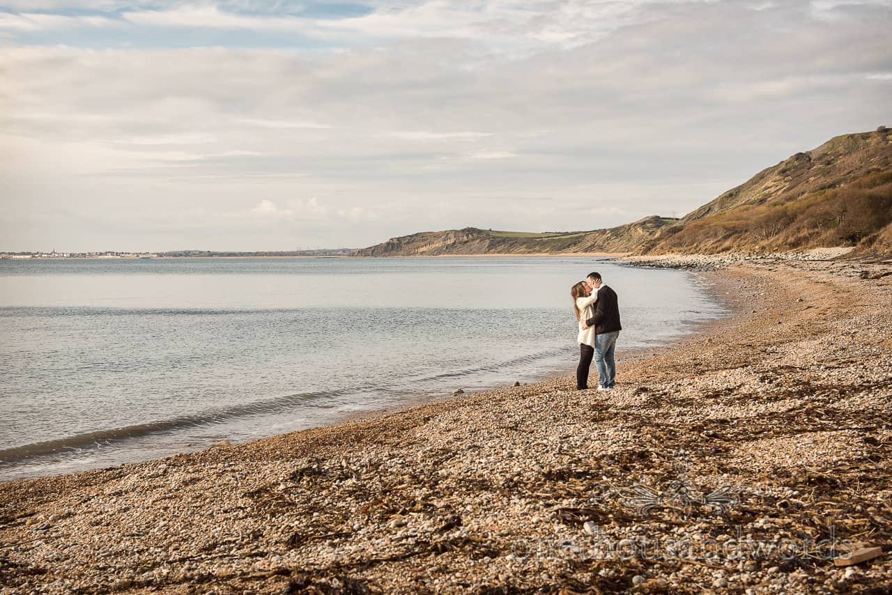 Engagement photograph of intimate kissing moment between newly engaged couple on Dorset beach by one thousand words