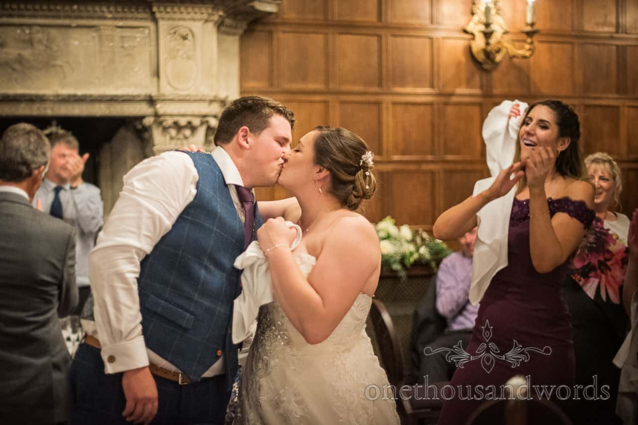 Kissing bride and groom are applauded by wedding guests during singing waiters performance at Rhinefield House hotel