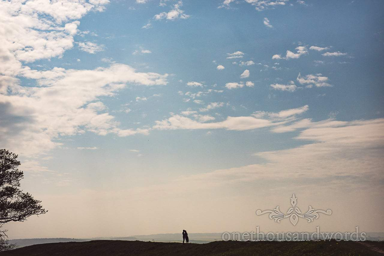 Engagement photograph silhouette of couple kissing with big blue sky in Dorset countryside