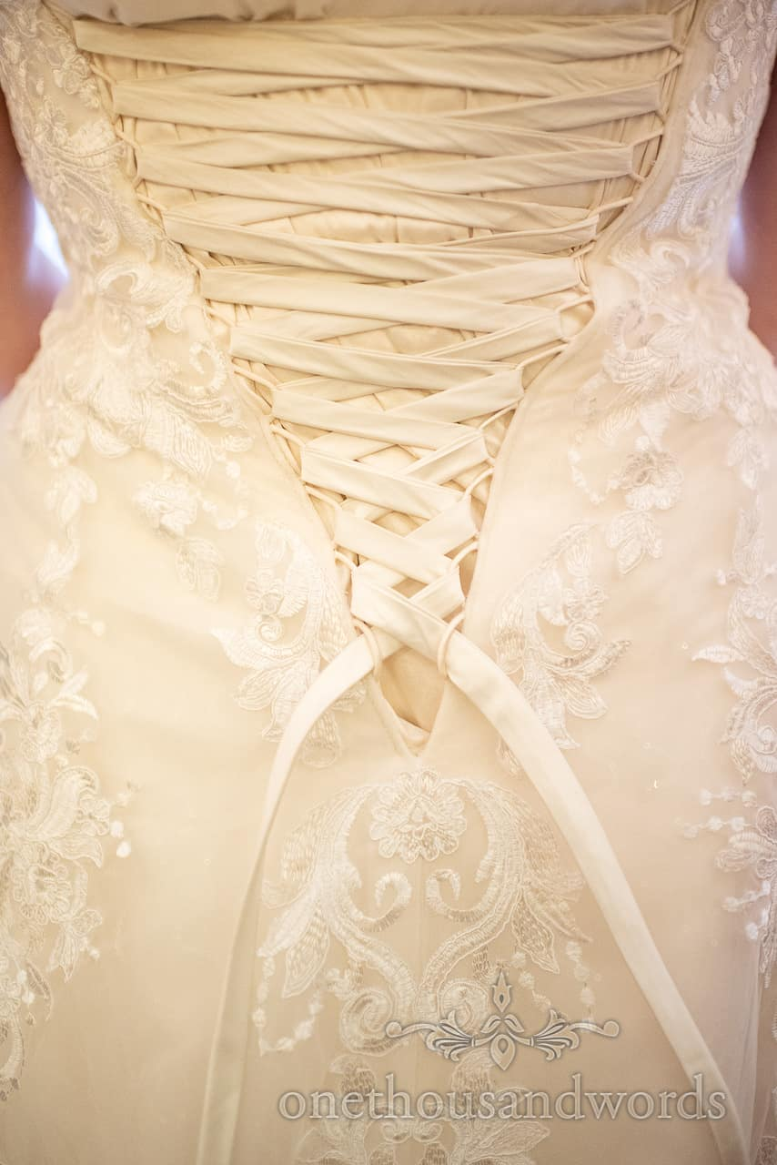 Close up lacing detail photograph of the back of a white wedding dress by one thousand words wedding photography