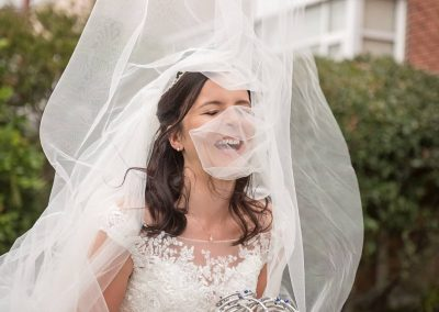 Laughing bride with white veil blowing in the wind at wedding documentary photograph by Dorset wedding photographers