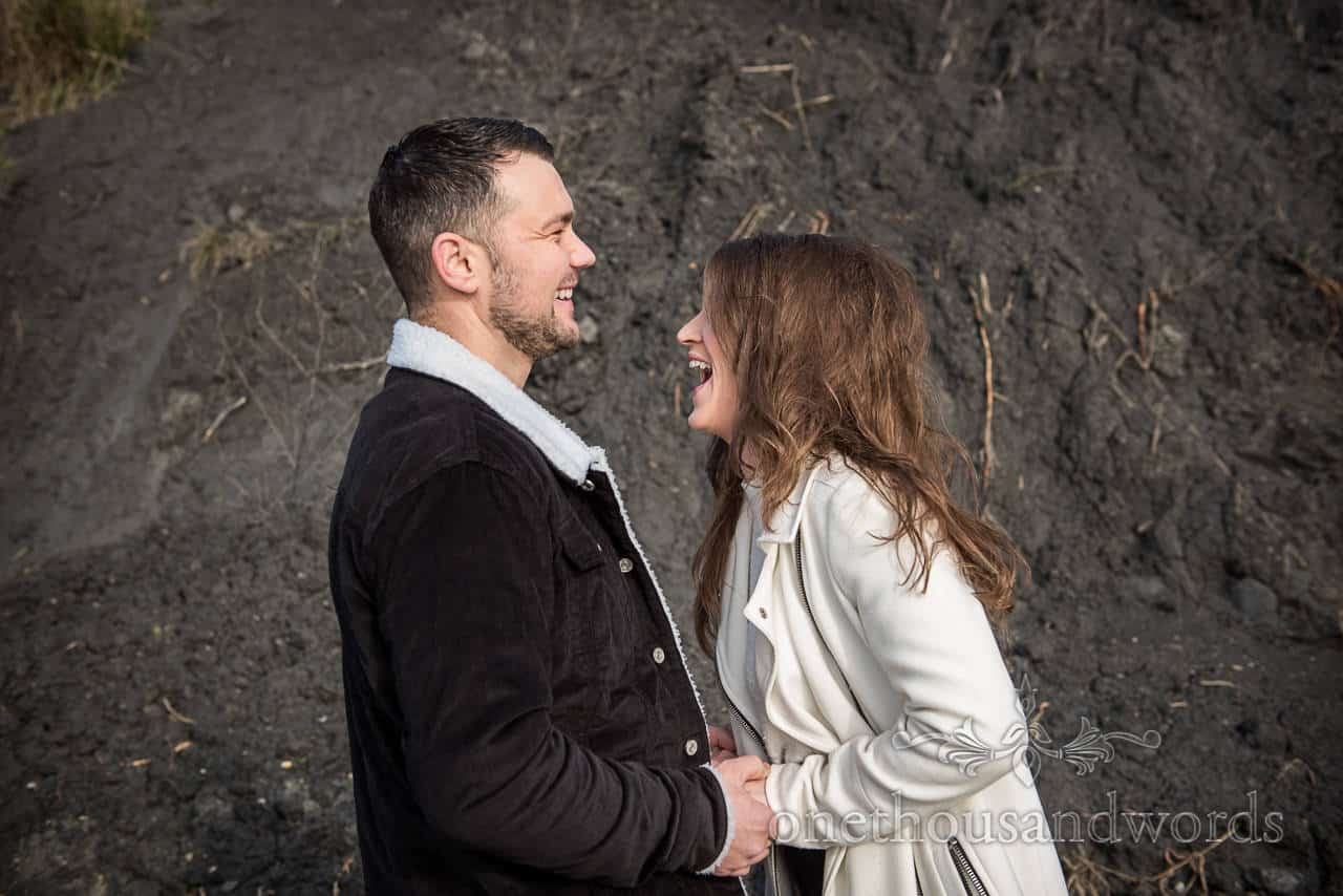 Laughing couple at engagement shoot photo taken against black cliff mud by one thousand words wedding photography