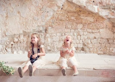 Cute laughing flower girls sitting on stone castle venue wall with camera by one thousand words photography