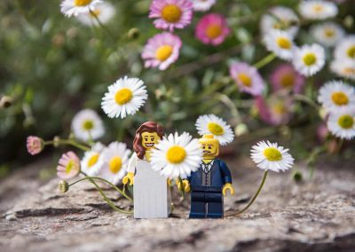 Lego bride and groom on stone wall flower bed comedy wedding close up photo by one thousand words wedding photography