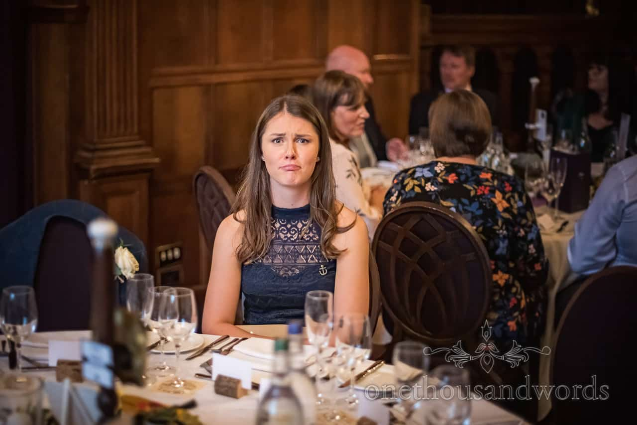 Lonely wedding guest pulls a sad face at an empty table at Rhinefield House hotel wedding breakfast photographs