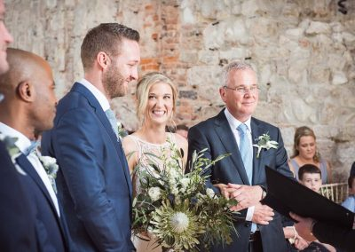 Lulworth Castle civil wedding ceremony photograph of happy bride and groom with huge green South African flower bouquet