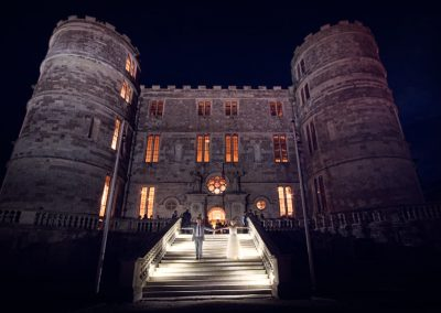 Lulworth Castle lit at night with bride and groom photographed by wedding photographers one thousand words