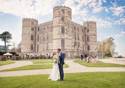 Lulworth Castle summer wedding venue with kissing bride and groom photographs by one thousand words wedding photography