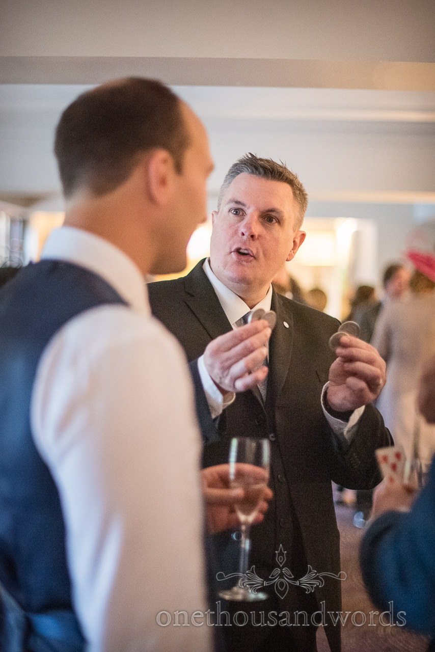 Wedding magician shows coin trick to wedding guests during drinks reception photographs