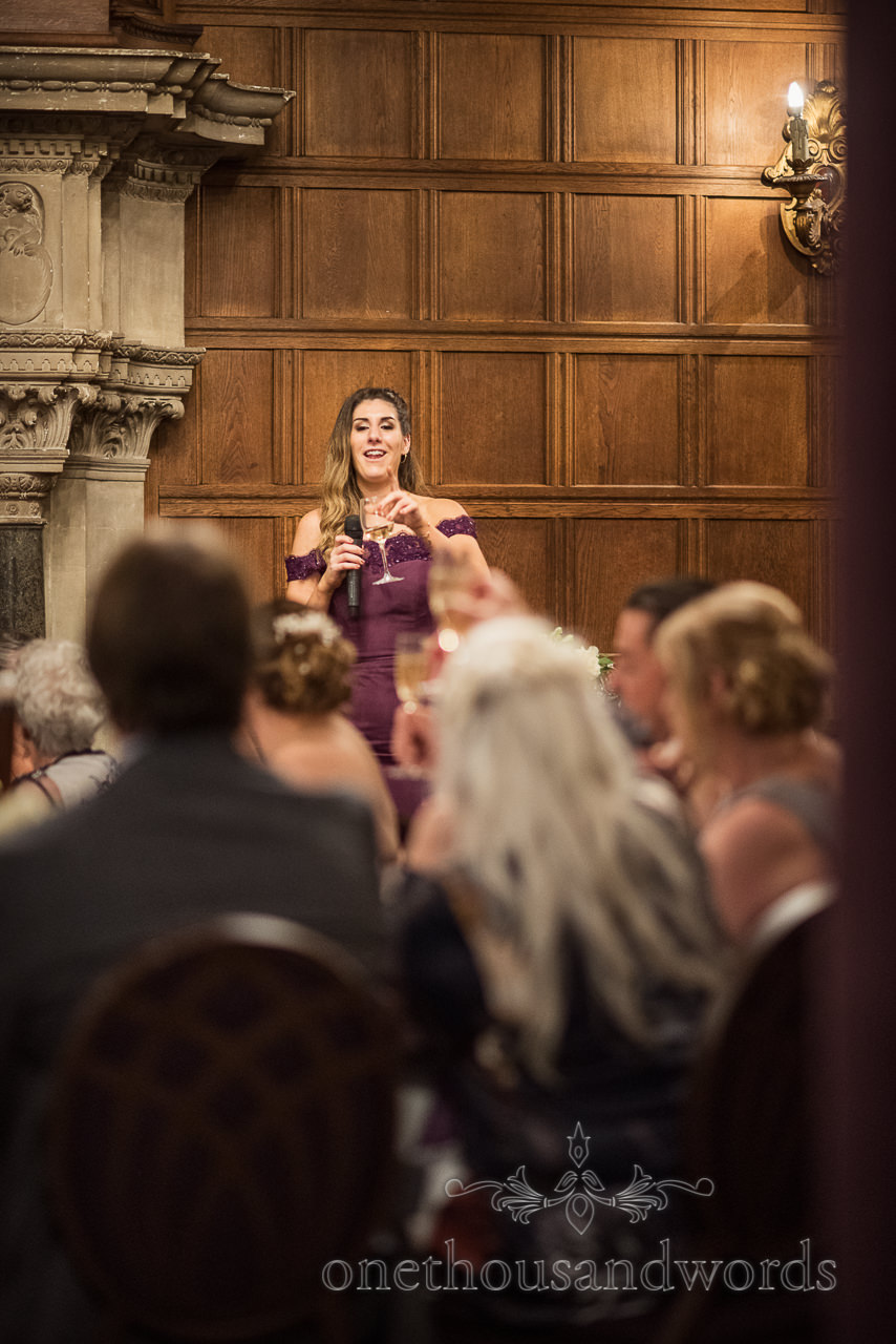 Maid of honour in purple dress makes wedding speech against wood panelling whilst holding glass of wine