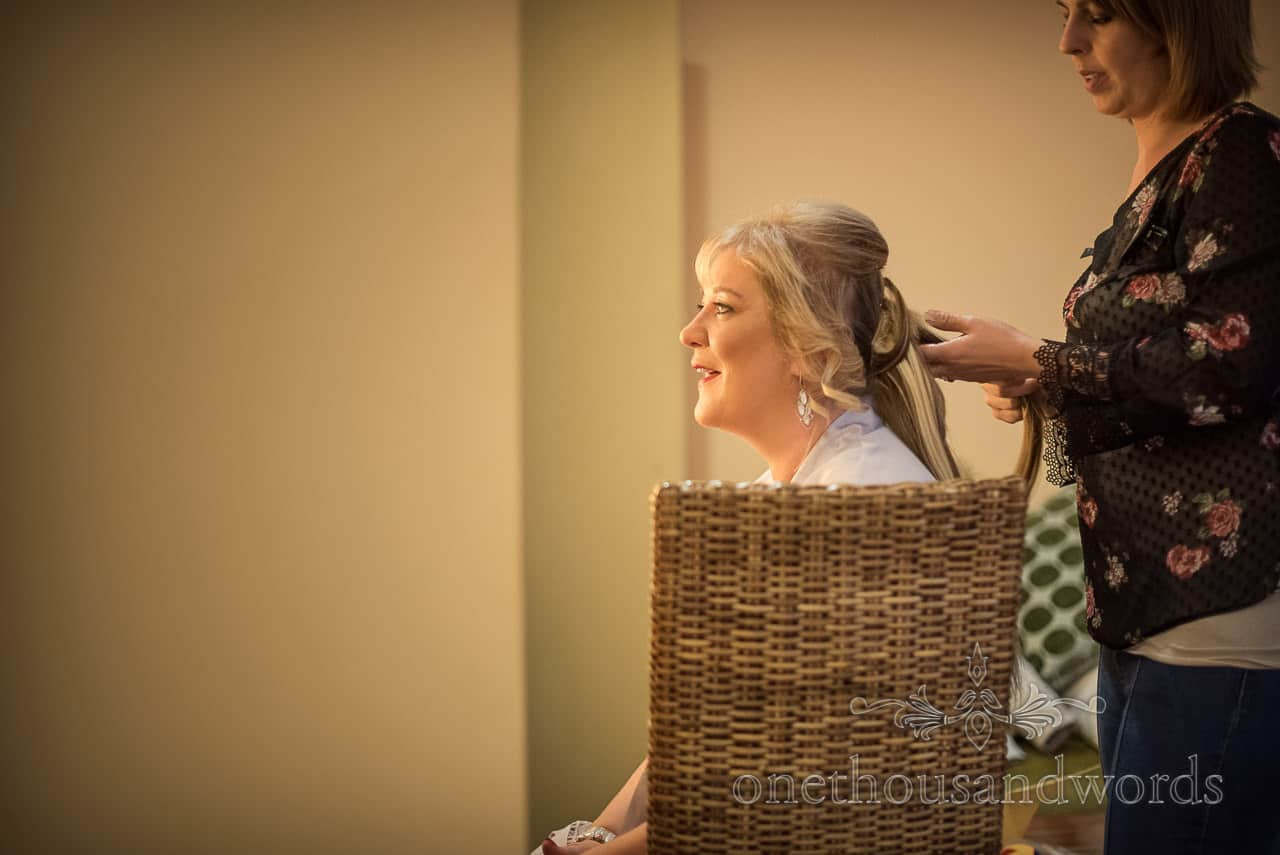 Mother of the bride has her hair styled on wedding morning during bridal preparation photographs