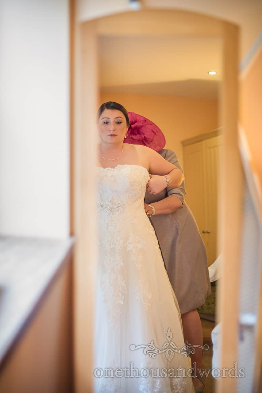 Bride looks in full length mirror as mother in pink hat helps lace her into wedding dress during bridal preparation