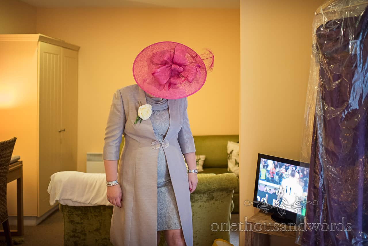 Documentary wedding photograph of mother of the bride wearing pink hat and grey dress and jacket on wedding morning