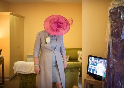 Mother of the bride in pink hat with silver outfit during wedding morning coverage by one thousand words photography
