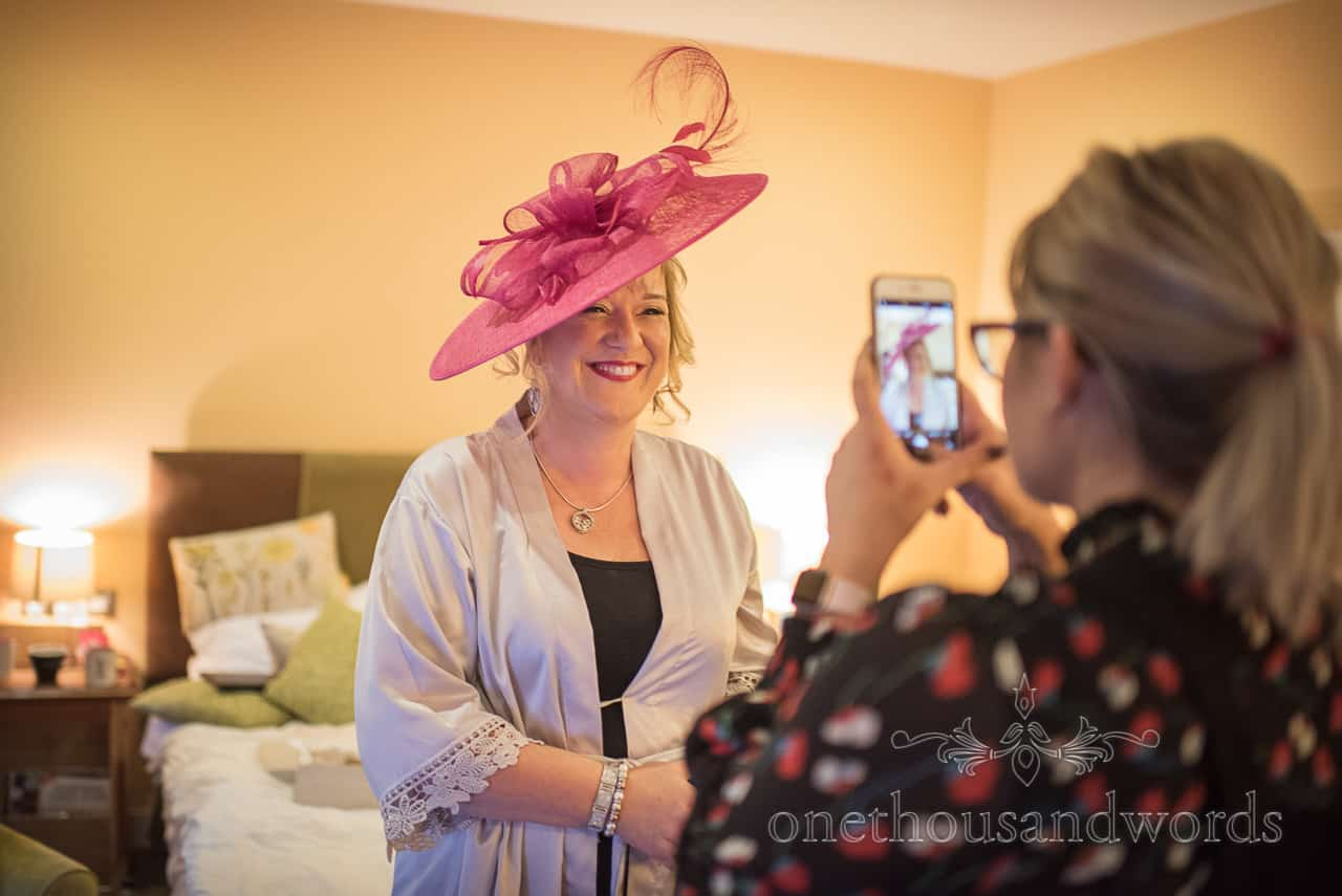 Happy mother of the bride wearing pink wedding hat has her photograph taken on mobile phone
