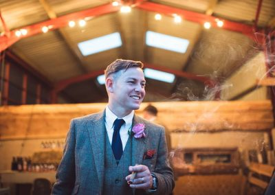 Natural groom portrait photograph with cigar at farm barn on wedding evening photographed by one thousand words photography