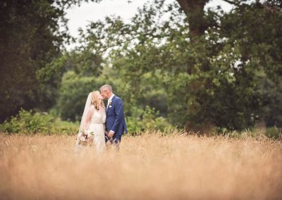 Natural wedding couple kissing in English countryside field by wedding photographers one thousand words