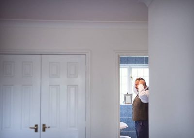 Natural wedding photograph of grooms man styling hair in doorway during wedding morning preparation photos