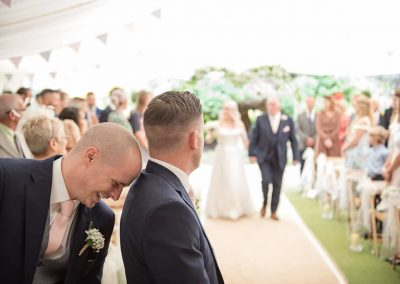 Best man laughing on grooms shoulder at Parley Manor wedding ceremony photographed by one thousand words photography