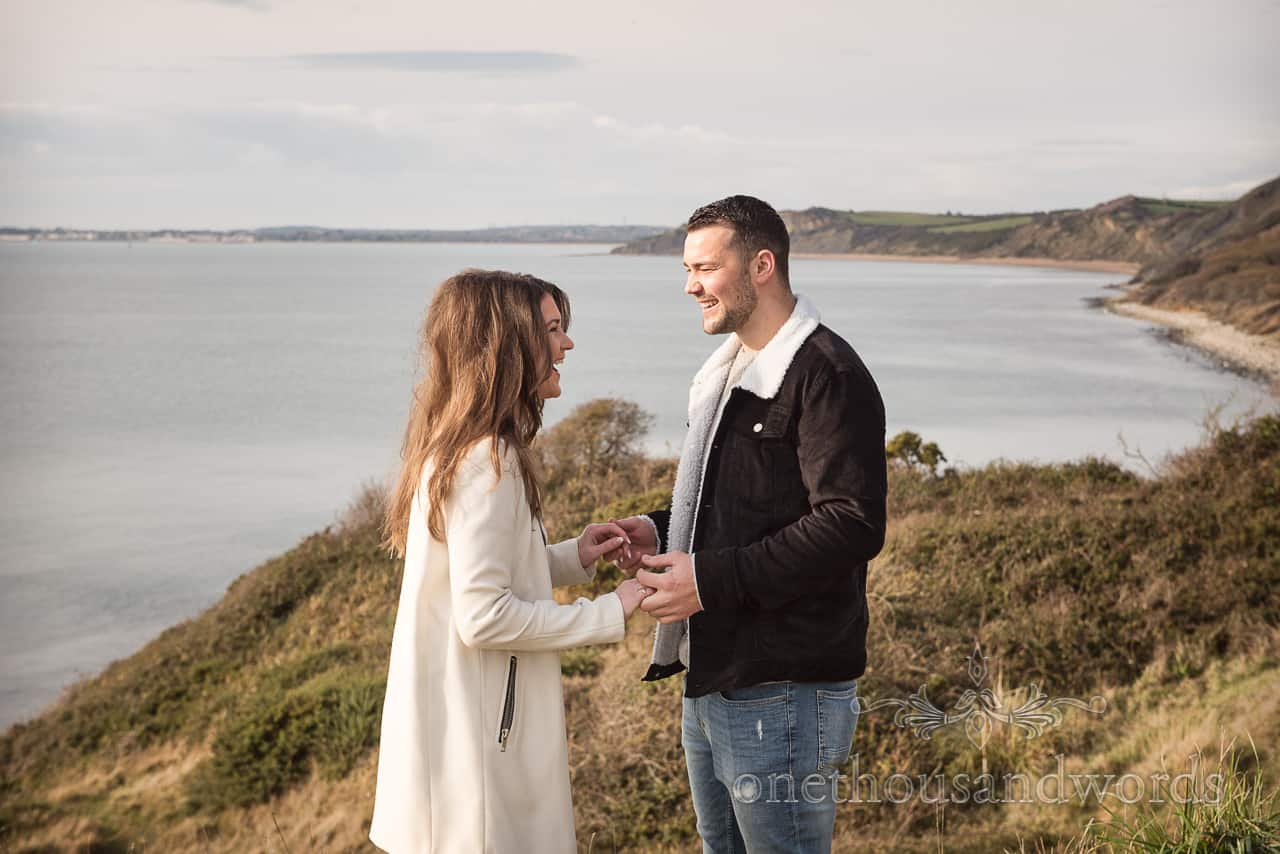 In love newly engaged couple laughing with Dorset coast sea side view photograph by one thousand words wedding photography