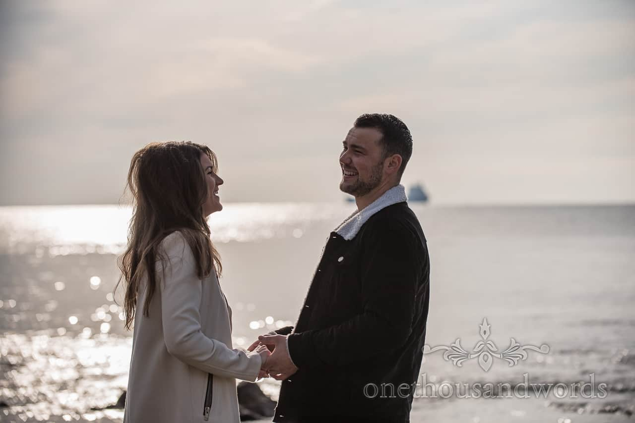 Newly engaged couple laughing at Dorset seaside by one thousand words documentary wedding photography in Dorset