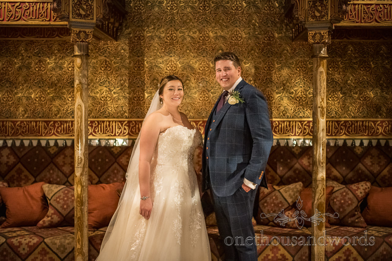 Wedding photograph of newlywed bride and groom in Rhinefield House hotel's golden detailed Alhambra room
