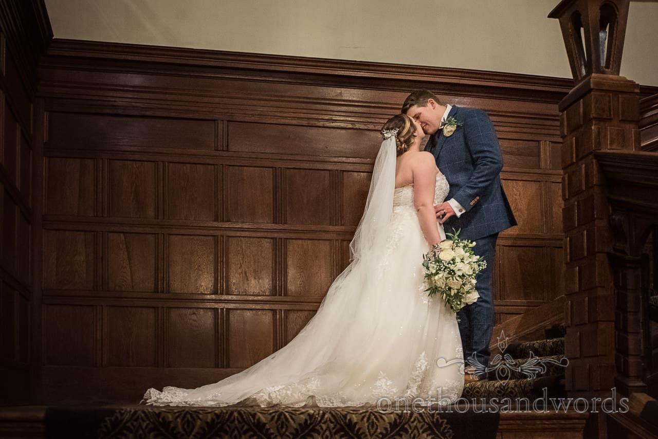 Newlywed bride and groom kissing on wooden panelled hotel staircase at Rhinefield House hotel in New Forest