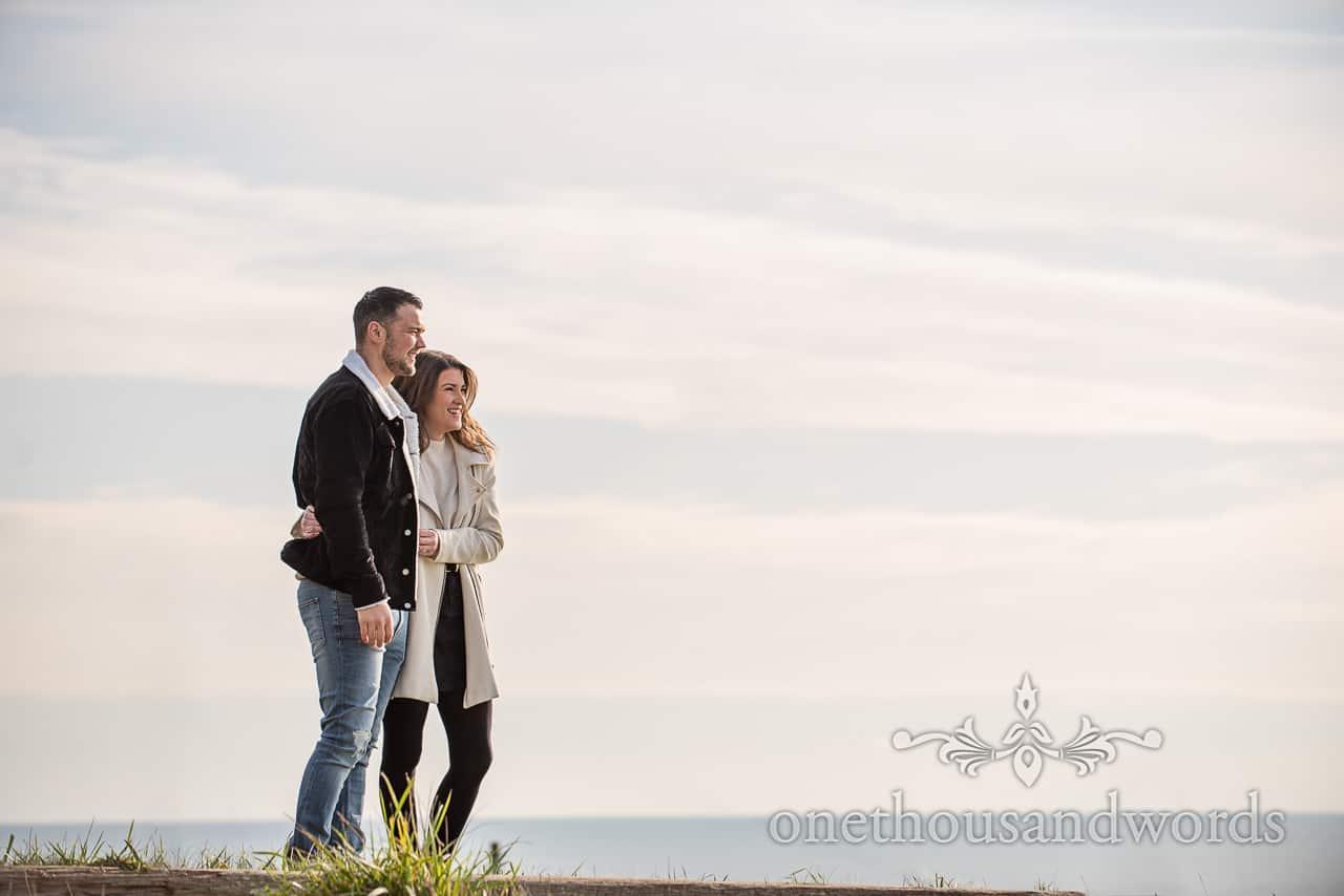 Osmington Mills engagement photographs couple admiring coastal views by one thousand words wedding photography in Dorset
