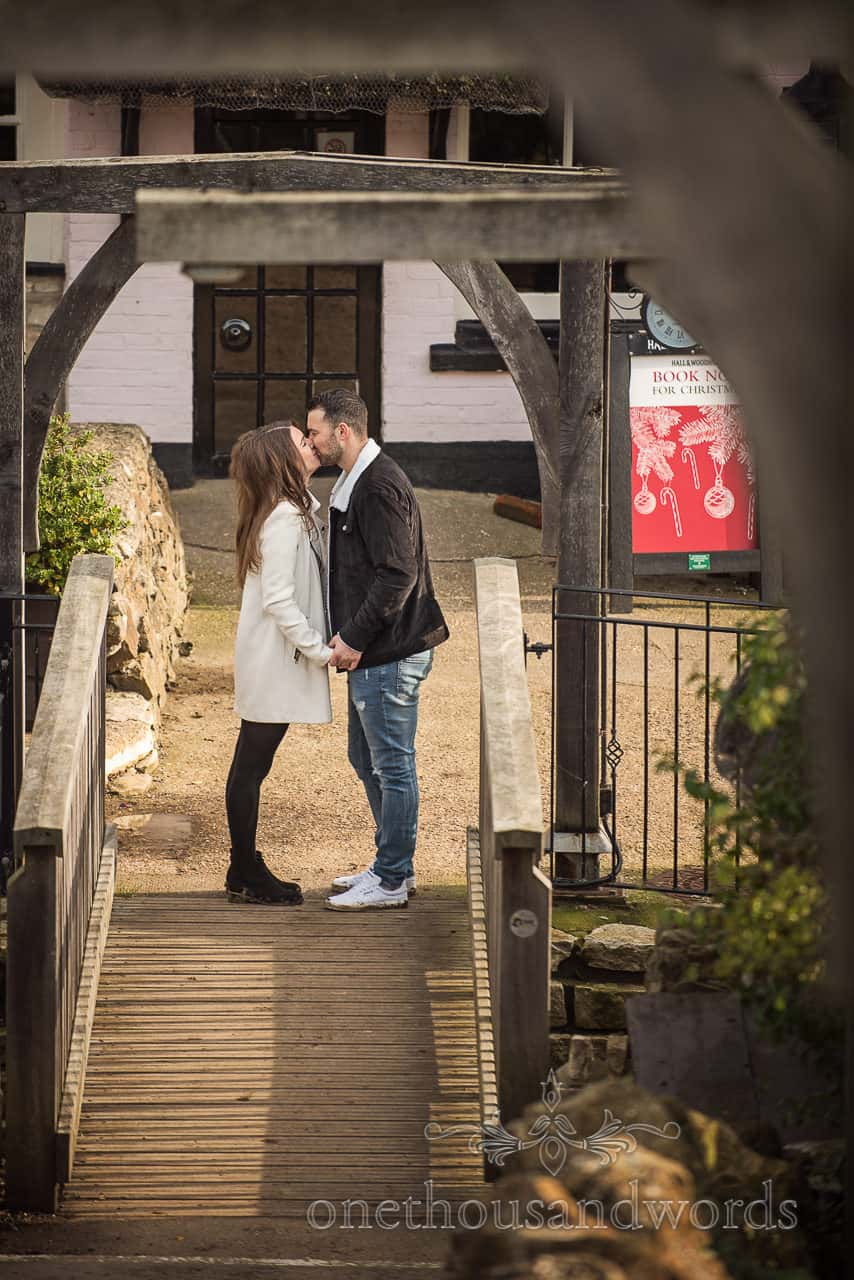Osmington Mills engagement photo of couple kissing at Smugglers Inn Dorset pub by one thousand words wedding photography