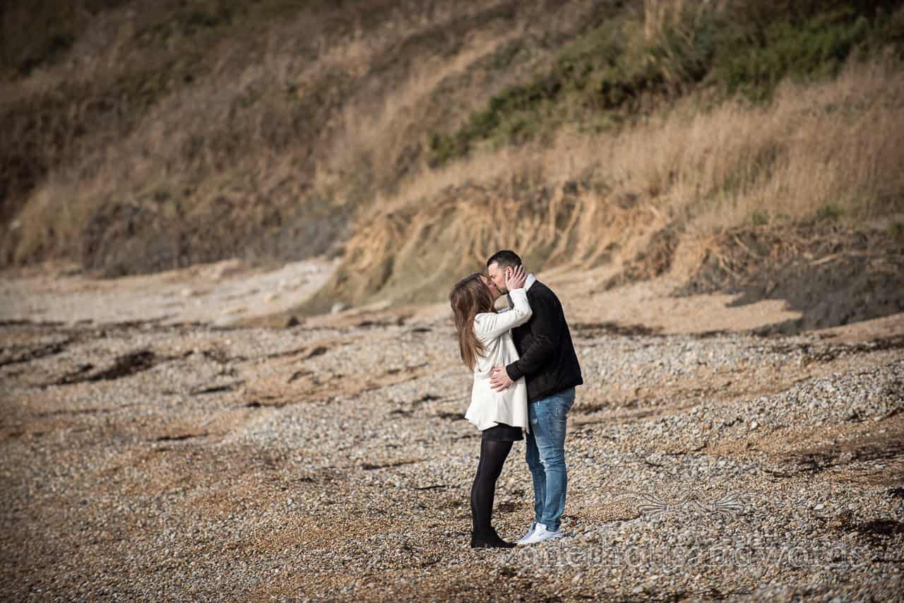 Osmington Mills engagement photographs of couple kissing on Dorset beach by one thousand words wedding photography in Dorset