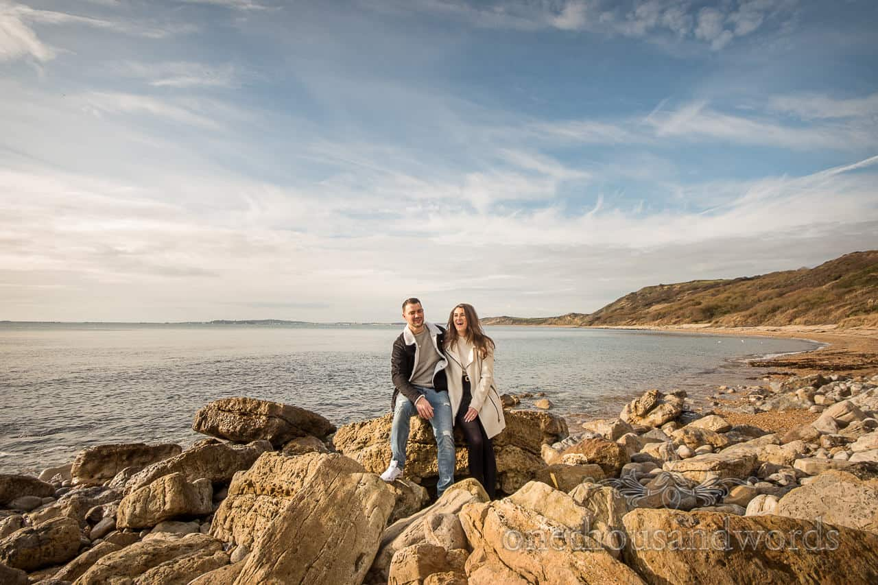 Osmington Mills engagement photographs of couple sat on Dorset beach laughing by one thousand words wedding photography