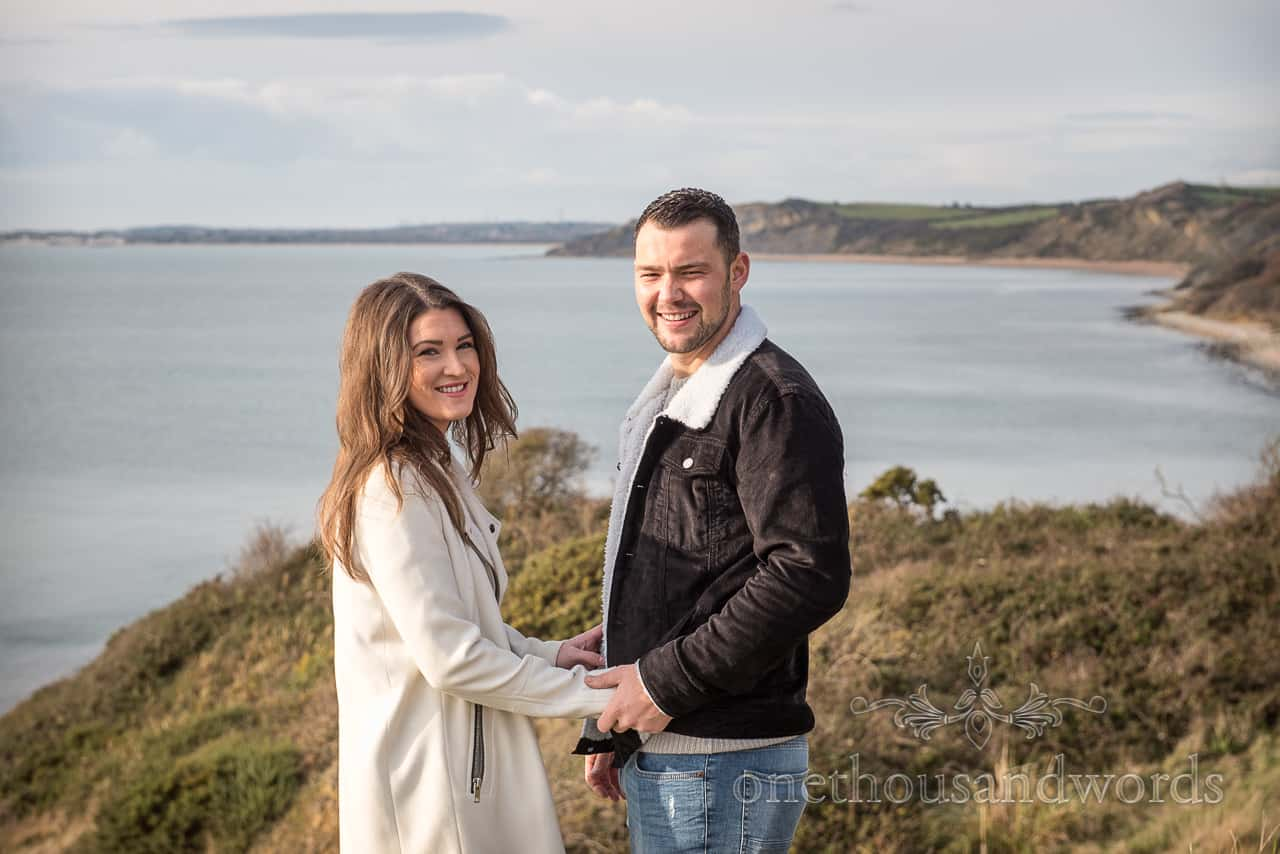 Osmington Mills engagement photographs of happy couple holding hands by one thousand words documentary photography